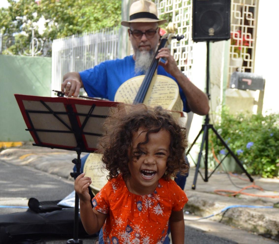 Una pequeña de la comunidad disfruta su contacto con el arte y la música mientras el chelista José Daniel de Jesús realiza una de sus interpretaciones. (Foto Alina Marrero para Fundación Nacional para la Cultura Popular)