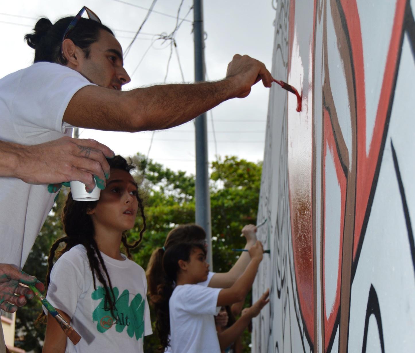 El artista enseña a una niña a cómo deslizar la brocha sobre una pared convertida en lienzo. (Foto Alina Marrero para Fundación Nacional para la Cultura Popular)