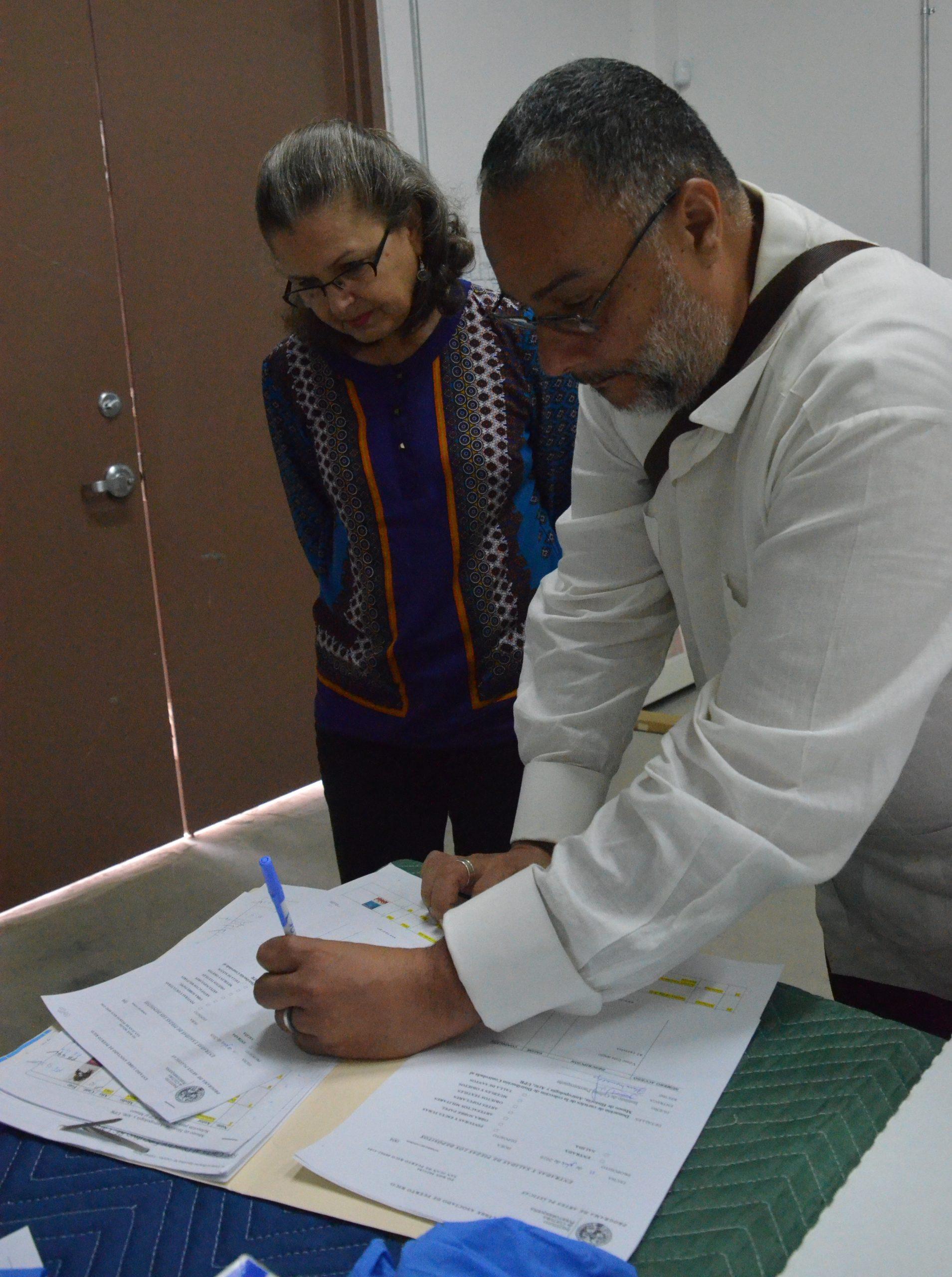 Jorge Irizarry Vizcarrondo, director ejecutivo del Instituto de Cultura Puertorriqueña, y Flavia Marichal del Museo de Historia, Antropología y Arte de la Universidad de Puerto Rico, firman acuerdo para oficializar la donación de carteles. (Foto suministrada)
